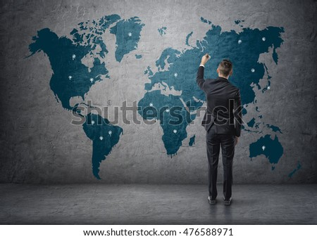 Back view of a businessman making marks on world map. Global communication. International relations. Business staff. #476588971