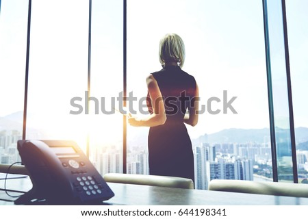 Back view of a businesswoman with digital tablet in hands is watching in office window on a Hong Kong city view and thinking about future her company. Female manager is using touch pad during work day stock photo