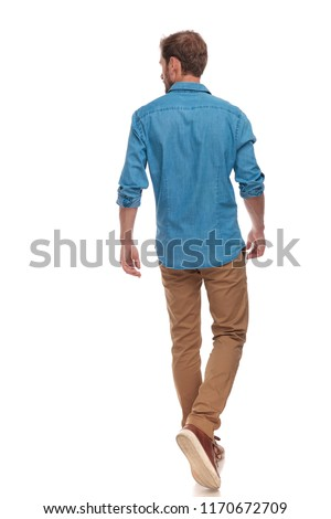back view of a casual young man walking and looking to side on white background