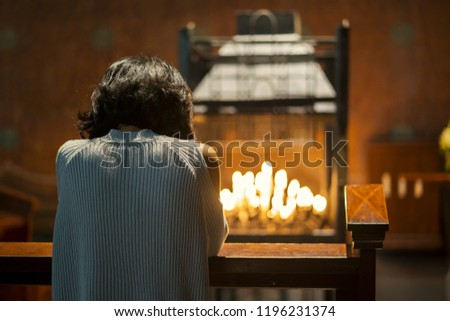 Back view of a Christian woman sitting in the church while praying to the GOD #1196231374