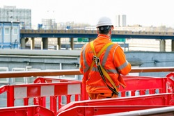 Back view of a construction worker walking into a building site in Canary Wharf, London