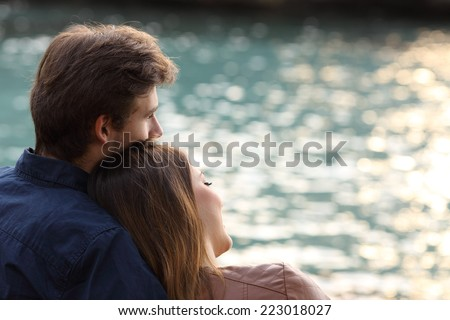 Back view of a couple hugging and watching the sea on the beach at sunset