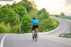 back view of a cyclist on top of a mountains winding road, riding a black bicycle down a hill, wearing bike helmet and blue cycling jersey, with grey clouds sunset sky and forest in the background.