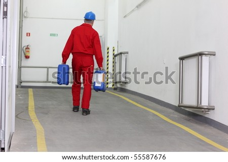Back view of a factory worker carrying two blue bottles of chemicals in a factory.
