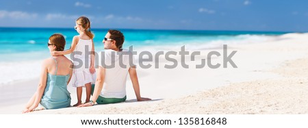 Back view of a family on a tropical beach