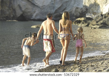 back view of a family walking on a beach