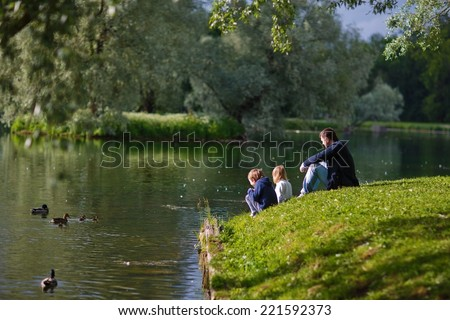 Back view of a father and his little kids sitting on the river shore and looking at ducks on a sunny spring day - stock photo
