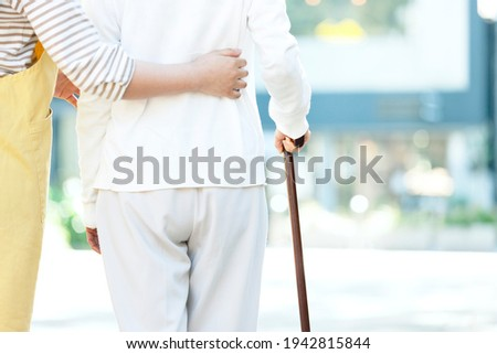 Back view of a female caregiver assisting senior women in walking Stock photo ©