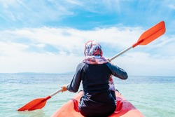 Back view of a fit young muslim woman kayaking on the beach. Woman paddling a kayak by the tropical beach. Kayaking tour in Phuket, Thailand. Travel concept.