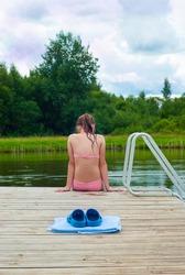 Back view of a girl in bikini sitting by the lake