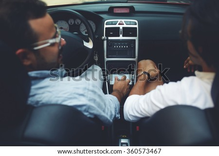 Back view of a handsome man convertible driver listening to the story of his friend while their travel together, two men sitting in luxury car cabriolet while having road trip during summer adventures