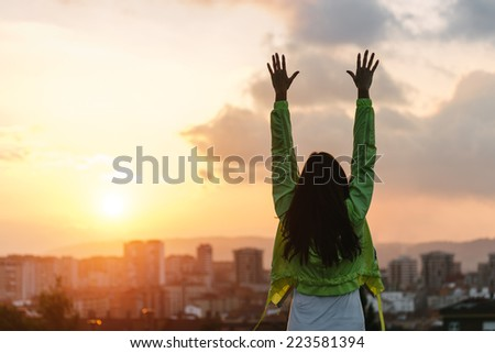 Back view of a happy woman celebrating sport goals and fitness lifestyle success. Female athlete raising arms to the sky after exercising towards beautiful sunset or morning over city skyline.