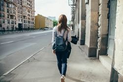 Back view of a hipster girl walking on city street