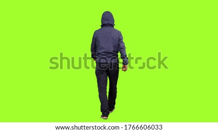 Photo of  Back view of a hooded man walks on green screen background, Chroma key