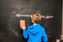 Back view of a little boy cleaning chalkboard.