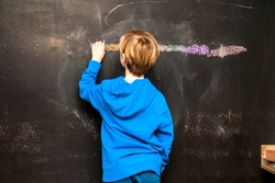 Back view of a little boy painting something on a chalkboard.