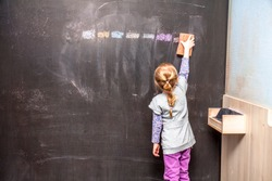 Back view of a little girl cleaning chalkboard.