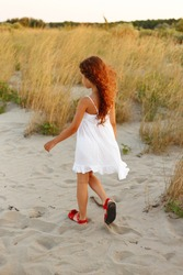 Back view of a little girl with curly hair walking at sand on the beach with a white dress, field background.