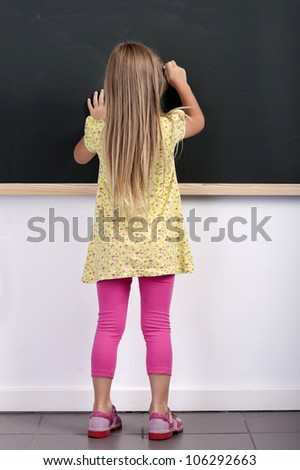 back view of a little girl writing on a chalkboard