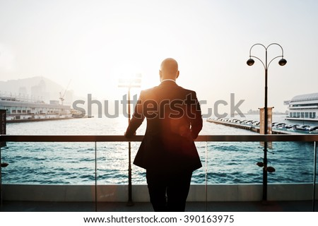 Back view of a male proud CEO is resting after work day, while is standing outdoors against sea port in evening. Silhouette of a young successful businessman in black suit is enjoying landscape