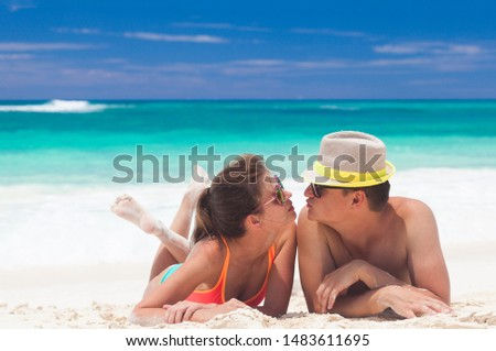 Back view of a man and woman couple relaxing on caribbean white sand beach #1483611695