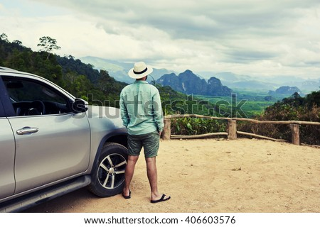 Back view of a man is thinking about this amazing world, while is standing on a mountain against jungle view. Young male traveler is enjoying beautiful landscape during road trip on suv in Thailand #406603576