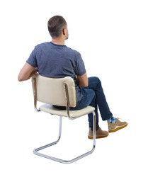 Back view of a man sitting on a chair. Rear view people collection. The guy sits cross-legged. backside view of person. Isolated over white background.