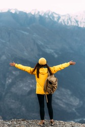 Back view of a man standing against the background of mountains with his arms outstretched. The man in the mountains raises his hands. Man on the background of mountains. Travel to the mountains