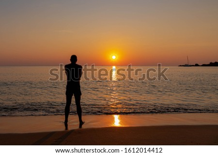 Back view of a man standing on beach watching sunset in tropical island, Silhouette of a men looking the sun going down on seashore with golden colour skyline in the evening.