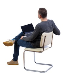 Back view of a man who sits on a chair with a laptop.  Rear view people collection.   Isolated over white background. A man in yellow shoes is laying his laptop on his feet looking forward.