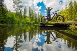 Back view of a modern e-mtb electric cyclist stretching or refreshing on a beautiful lake of Podolerteich, hidden gem in the middle of a forest.