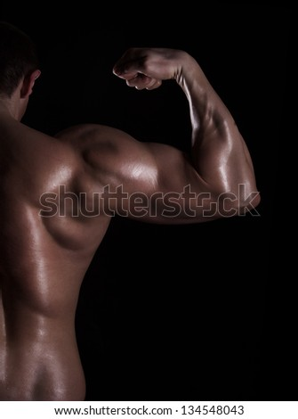 back view of a muscular young man showing his biceps isolated on black background