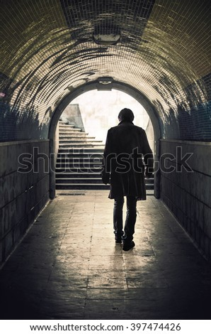 Back view of a mysterious man walking in a padestrian tunnel