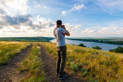 Back view of a photographer taking pictures of river landscape
