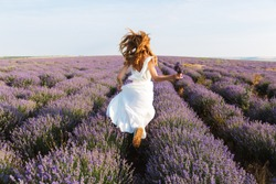 Back view of a pretty young girl in dress running at the lavender field
