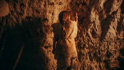 Back View of a Primitive Prehistoric Neanderthal Child Wearing Animal Skin Draws Animals and Abstracts on the Walls at Night. Creating First Cave Art with Petroglyphs, Rock Paintings.