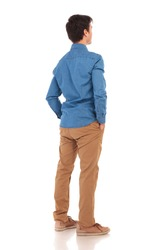 back view of a relaxed casual man with hands in pockets, full body picture of white background