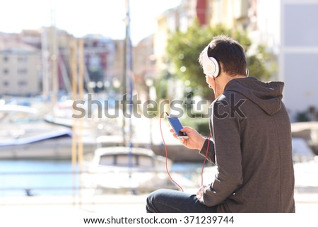 Back view of a teenager listening music with headphones from a smart phone on a vacations destination