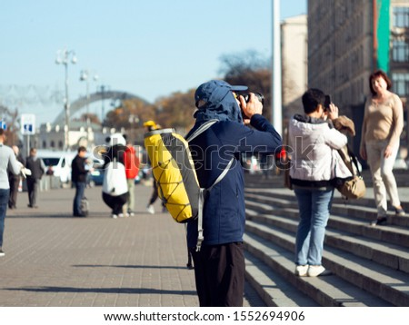Back view of a tourist who photographs the city.
