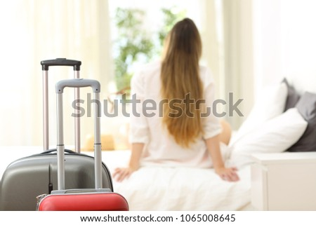 Back view of a traveler relaxing looking through a window in an hotel room after arrival with suitcases in the foreground #1065008645