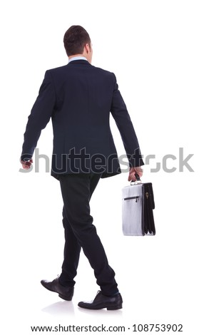 back view of a walking business man holding a briefcase and looking to his side on white background - stock photo