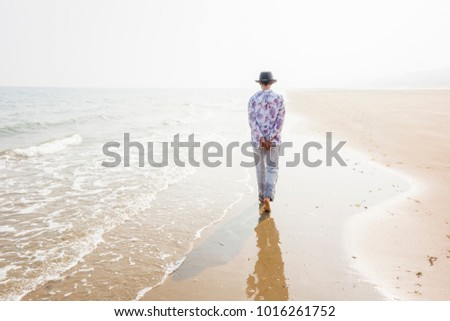Back view of a woman in introspection walking on the beach in summer. Image with high-key lighting representing solitude and tranquility, Saint-Laurent-sur-Mer, Calvados, Normandy, France