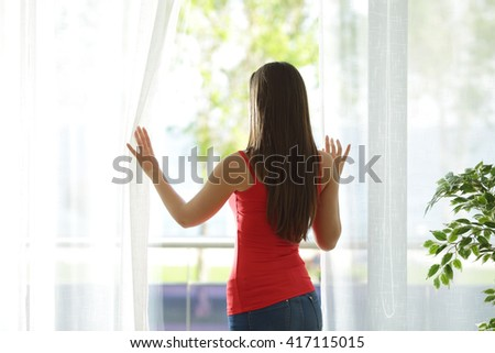 Back view of a woman looking outdoors through a window and opening curtains at home