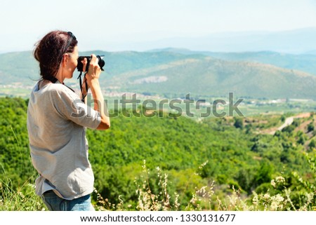 Back view of a woman photographer taking pictures of the valley with mountains from above. Europe. Greece.