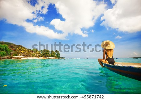 back view of a woman sailing a boat in a paradise island