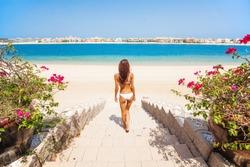 Back view of a woman walking towards the sea in Palm Jumeirah, Dubai