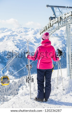 Back view of a woman with ski against a ski-lift and wonderful winter mountains backgroundagainst wonderful winter mountains background and , Zellertal, Austria