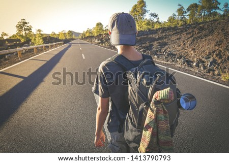 Back view of a young boy walks alone in the middle of the street. Teen with backpack leaving after the end of school Man walking to a new travel adventure. Positive, brave, and adventurous concept. #1413790793