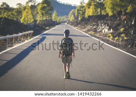 Back view of a young boy walks alone in the middle of the street. Teen with backpack leaving after the end of school Man walking to a new travel adventure. Positive, brave, and adventurous concept. #1419432266