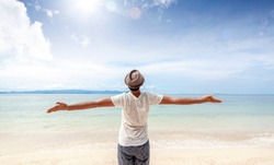 Back view of a young casual man at the seaside holding both hands in the air celebrating life and freedom.